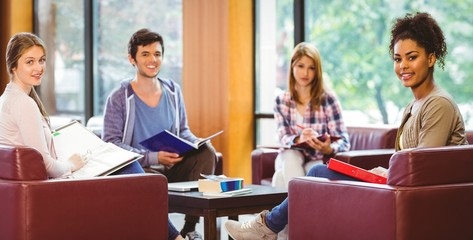 Students sitting on couch revising and smiling at camera