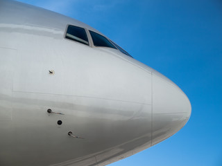 Airplane nose close up isolated on blue sky