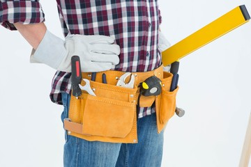 Repairman wearing tool belt while standing with hands on hips