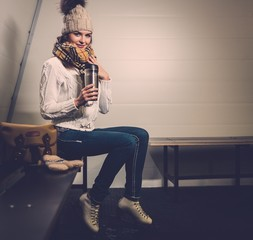 Cheerful girl with mug of hot drink in ice rink locker room