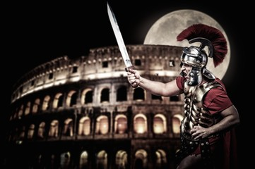 Roman legionary soldier in front of coliseum at night time