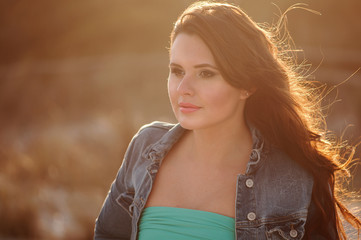 Beautiful young woman on the sunset beach, outdoor image