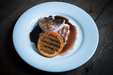 Grilled meat with orange on white ceramic plate on old wooden ta