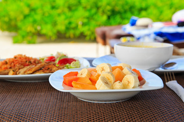 fruit salad, soup and chicken rice served on beach restaurant