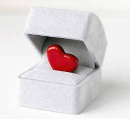 A bright red heart in a grey jewelry box