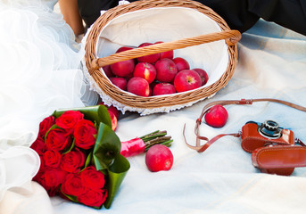 wedding picnic with apple, bouquet of rose and old camera