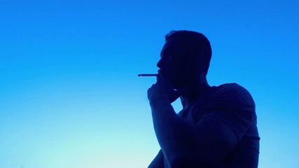 Young man smoking, relaxing at sunset