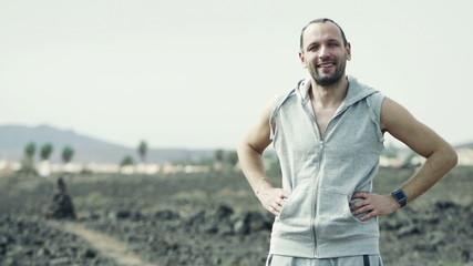 Portrait of happy, smiling male jogger on desert, slow motion