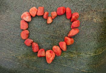 Rotes Herz aus Kieselsteinen auf  Felsen