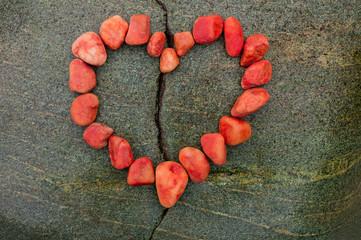 Zerbrochenes Herz aus Kieselsteinen auf  Felsen