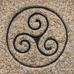 Symbol Triskel in Granit gemeißelt