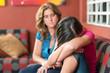 Sad teenage girl cries next to her worried mother