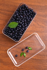 blueberries, currant with leaf in box on wooden background