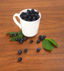 blueberries, currant with leaf in bowl, cup on wooden background