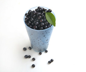 blueberries with leaf in bowl, cup on white background