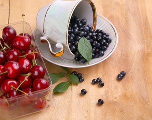 blueberries with leaf in cup and cherry in box on wood