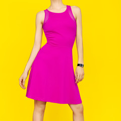 Girl in bright pink summer dress on yellow background