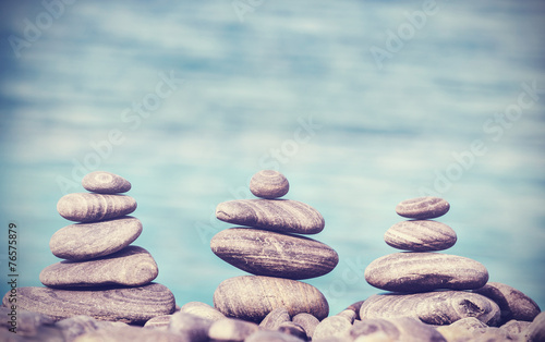 Vintage retro hipster style image of stones on beach, Zen spa co - 76575879