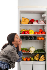 hungry woman and a fridge full of food