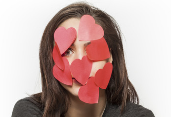 Girl with face covered with paper hearts