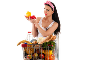 woman sitting in supermarket trolley with pepper in the hands