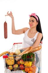woman sitting in a supermarket trolley with sausage in hand