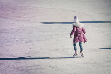 little girl in winter clothes skating on ice rink