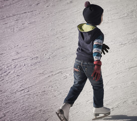 little boy in winter clothes skating on ice rink
