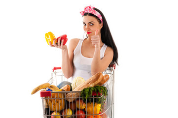 beautiful woman sitting in supermarket trolley with pepper