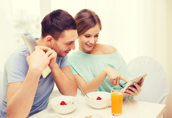 smiling couple with tablet pc reading news