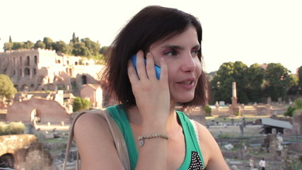 woman receives a call on his cell phone , near roman forum - steadycam