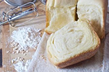 still life of bread, flour, kitchen utensil on a wooden board
