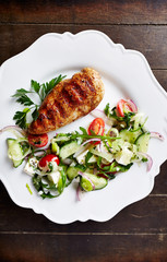 Grilled chicken fillet with salad and fresh herbs