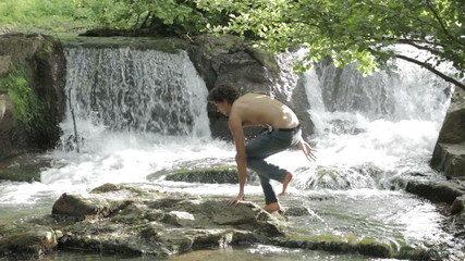 hiker cross the stream to sit on a rock and write in a notebook - waterfall