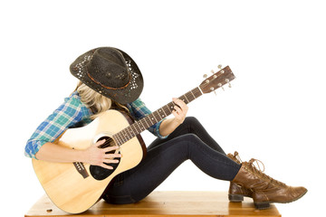 cowgirl with guitar in blue shirt sit knees