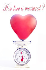 Love measure concept. Red heart balloon is weighted on scale