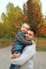 Папа с сыном на руках смотрят в даль в парке желтые листья