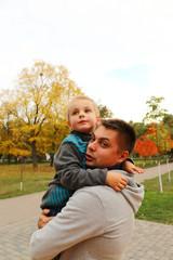 Папа с сыном на руках смотрят в даль осенью в парке