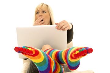 woman behind laptop yawning bright socks