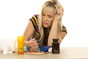 woman depressed with hand full of pills eyes closed