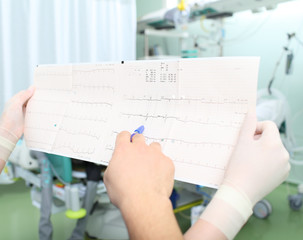 Close-up of two doctors interpretive cardiogram of patient in ho