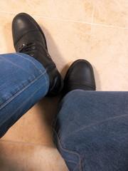 Ноги в джинсах и ботинках на кафельной плитке