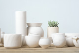 Unglazed white clay pots on wood table
