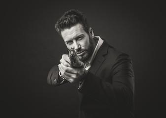 Cool handsome man pointing a gun