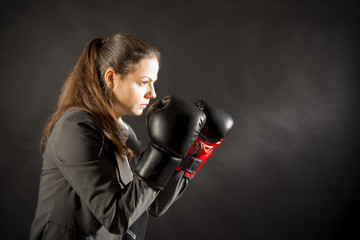Portrait of  young business woman wearing boxing gloves