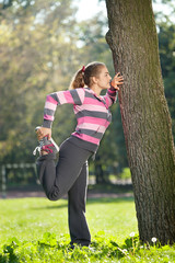 Young Beautiful Woman Stretching her Leg in the City Park