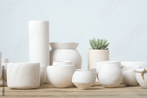 Leinwanddruck Bild Unglazed white clay pots on wood table