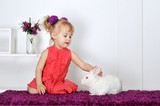 happy little girl with a small white rabbit