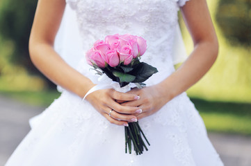 pink wedding bridal bouquet of roses in hands of the bride