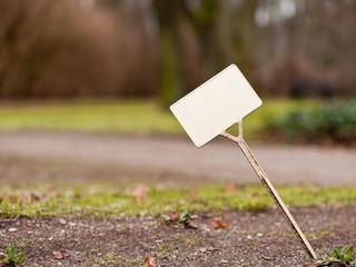Ein leeres helles Schild an einem Spiess steckt schief im Boden